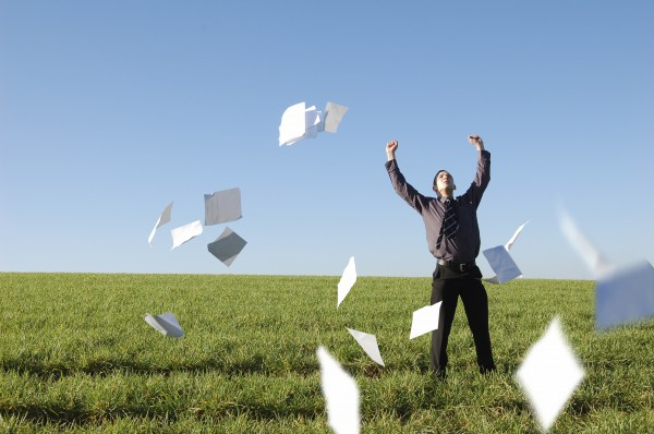 A happy businessman letting go of paperwork